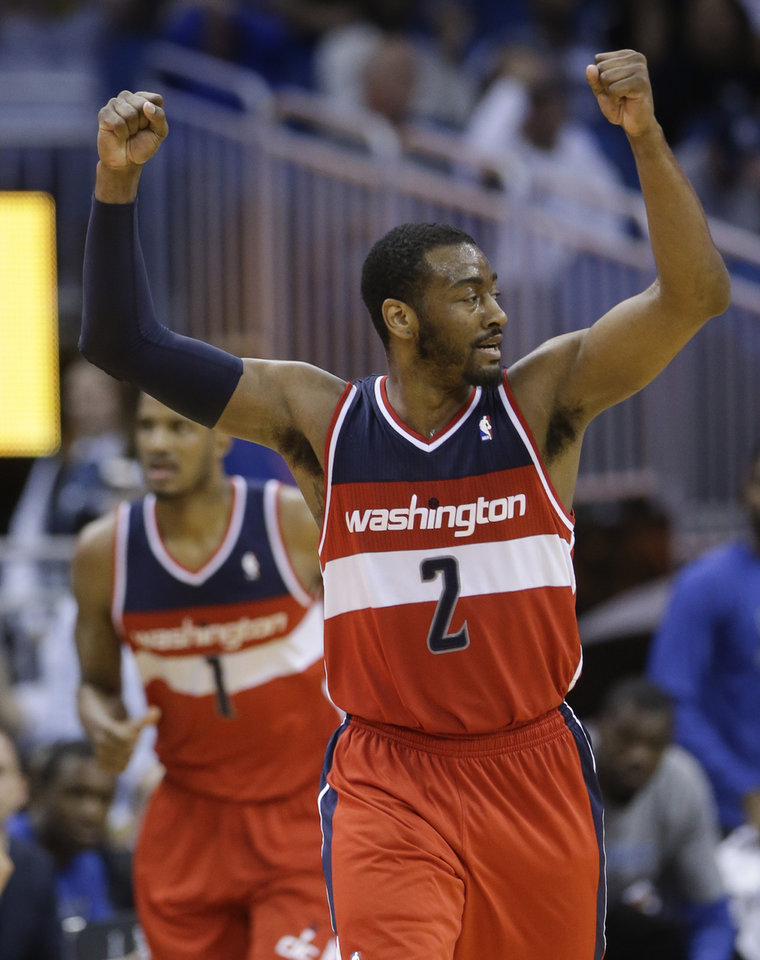 Photo - Washington Wizards' John Wall raises his arm as he runs down the court after teammate Trevor Ariza (1) made a 3-point shot against the Orlando Magic during the second half of an NBA basketball game in Orlando, Fla., Friday, March 14, 2014. Washington won in overtime, 105-101. (AP Photo/John Raoux)