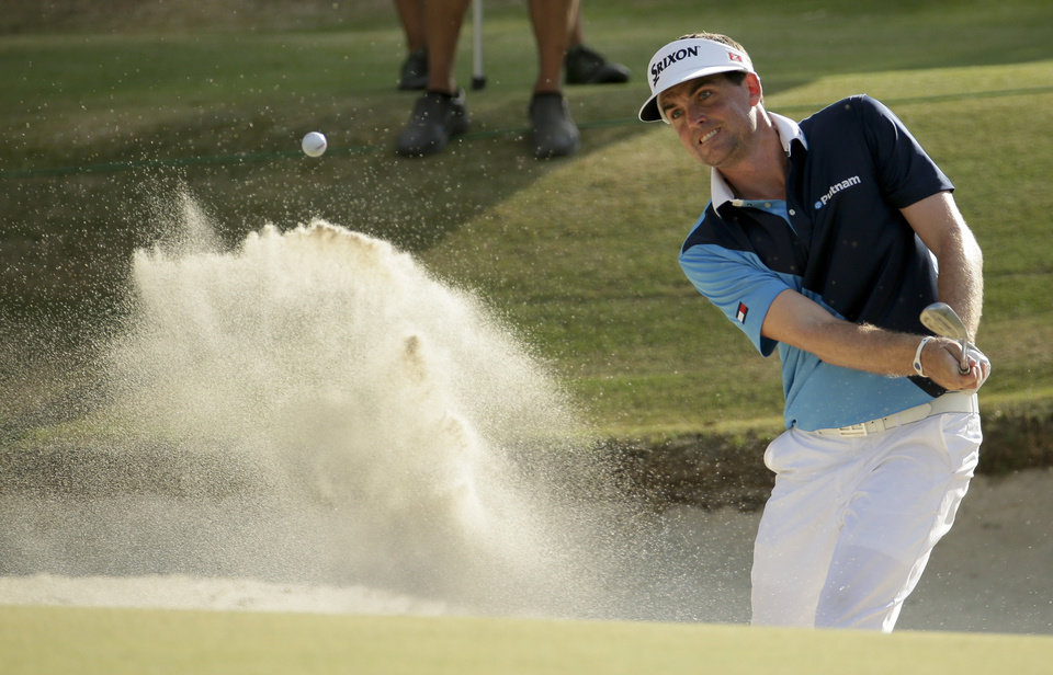 Photo - Keegan Bradley hits out of the bunker on the 16th hole during the first round of the U.S. Open golf tournament in Pinehurst, N.C., Thursday, June 12, 2014. (AP Photo/Charlie Riedel)