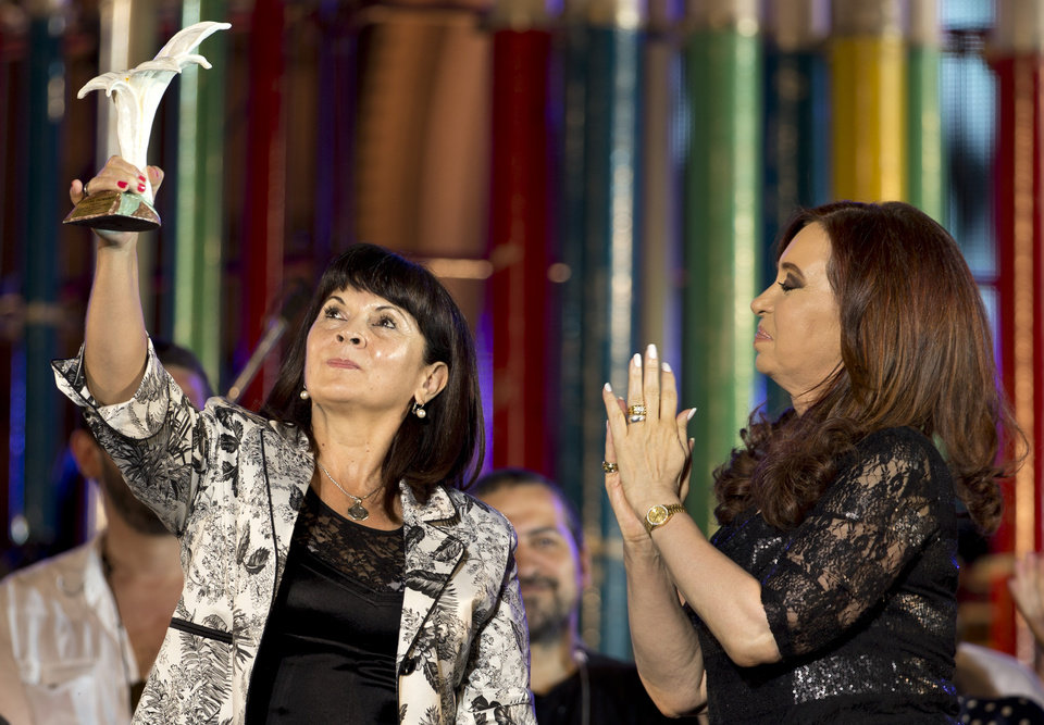 President Cristina Fernandez, right, applauds as Susana Trimarco, left, lifts a human rights prize given by the president during a rally to mark the 29th anniversary of the return to democracy in Argentina, on the eve of the Human Rights Day, in Buenos Aires, Argentina, Sunday, Dec. 9, 2012. Trimarco is known for her crusade to find her daughter, Maria de los Angeles