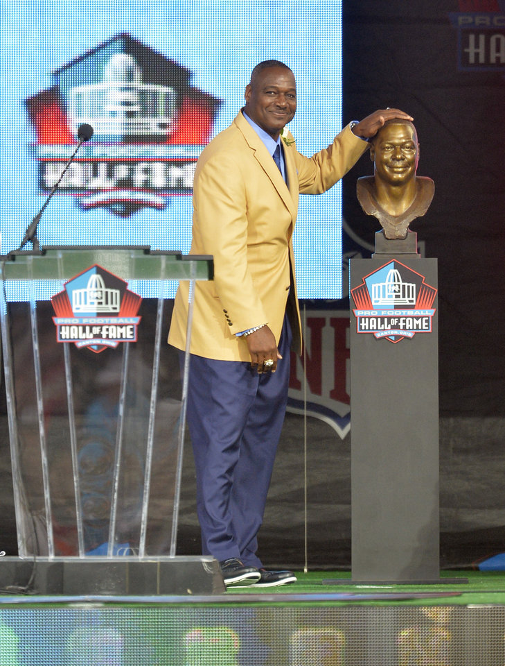 Photo - Hall of Fame inductee Derrick Brooks touches his bronze bust during the Pro Football Hall of Fame enshrinement ceremony Saturday, Aug 2, 2014, in Canton, Ohio. (AP Photo/David Richard)