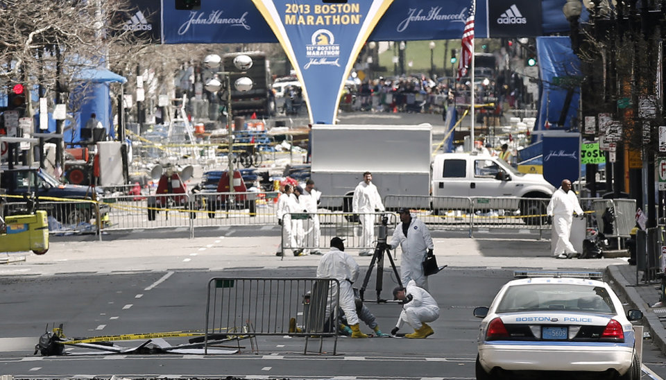 Investigators sift through evidence on Boylston Street just up from the finish line of the Boston Marathon in Boston, Thursday, April 18, 2013. (AP Photo/Winslow Townson)
