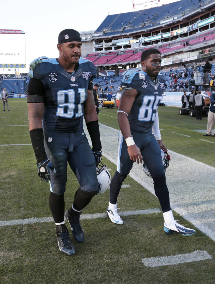 Photo - Tennessee Titans defensive end Derrick Morgan (91) and wide receiver Nate Washington (85) leave the field after the Jacksonville Jaguars defeated thems 29-27 in an NFL football game on Sunday, Nov. 10, 2013, in Nashville, Tenn. (AP Photo/Wade Payne)