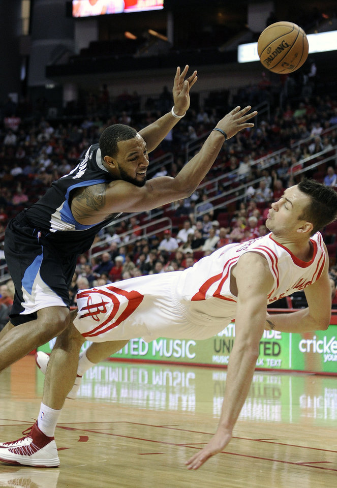 Photo - Houston Rockets' Donatas Motiejunas, right, is fouled by Minnesota Timberwolves' Derrick Williams, left, in the first half of an NBA basketball game Friday, March 15, 2013, in Houston. (AP Photo/Pat Sullivan)