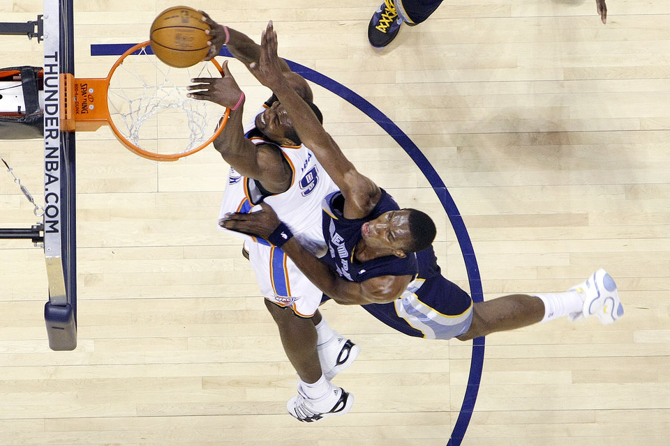 Photo - Thunder  forward Serge Ibaka is fouled by Memphis center Hasheem Thabeet during a 2010 game in Oklahoma City.    BY HUGH SCOTT, THE OKLAHOMAN