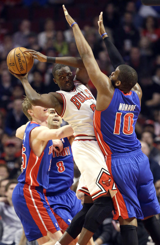 Photo - Detroit Pistons center Greg Monroe, right, and forward Kyle Singler, left, guard as Chicago Bulls forward Luol Deng, center, looks to pass during the first half of an NBA basketball game in Chicago on Sunday, March 31, 2013. (AP Photo/Nam Y. Huh)