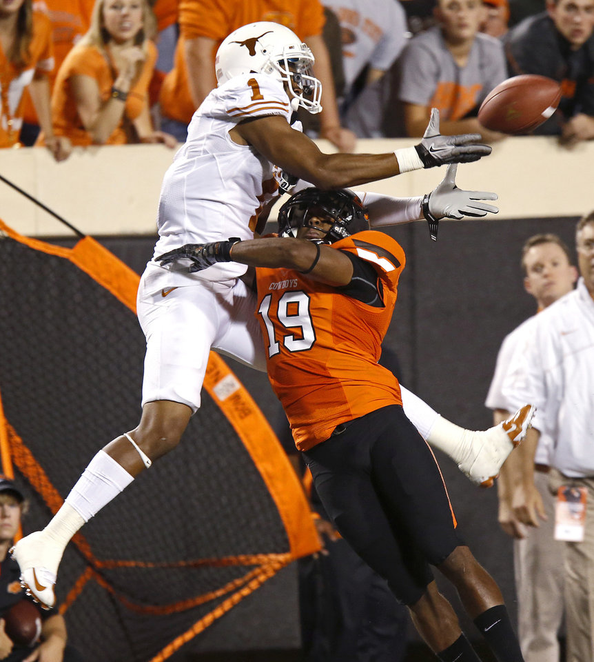 Photo - Oklahoma State's Brodrick Brown (19) is called for pass interference on Texas' Mike Davis (1) during a college football game between Oklahoma State University (OSU) and the University of Texas (UT) at Boone Pickens Stadium in Stillwater, Okla., Saturday, Sept. 29, 2012. Photo by Bryan Terry, The Oklahoman