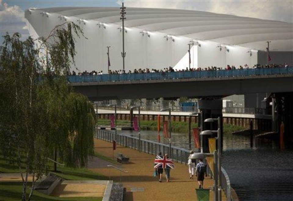Photo - In this Sunday, July 29, 2012 photo, a couple wearing a British flag walk near to the river as other visitors arrive at the Olympic Park during the 2012 Summer Olympics, in London. Patriotism and the games have always gone together, but gone are the days when one just waved a flag. Now flags are worn, seen all over London and especially at Olympic Park and other spots where the games are being played. (AP Photo/Emilio Morenatti)
