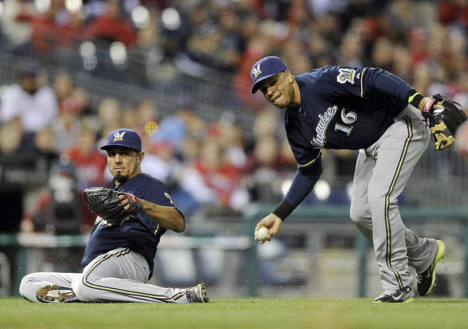 Photo - Milwaukee Brewers' third baseman Aramis Ramirez (16) picks up a ball bunted by Philadelphia Phillies' Ben Revere as Brewers' Matt Garza slides out the way during the fourth inning of a baseball game on Wednesday, April 9, 2014, in Philadelphia. (AP Photo/Michael Perez)