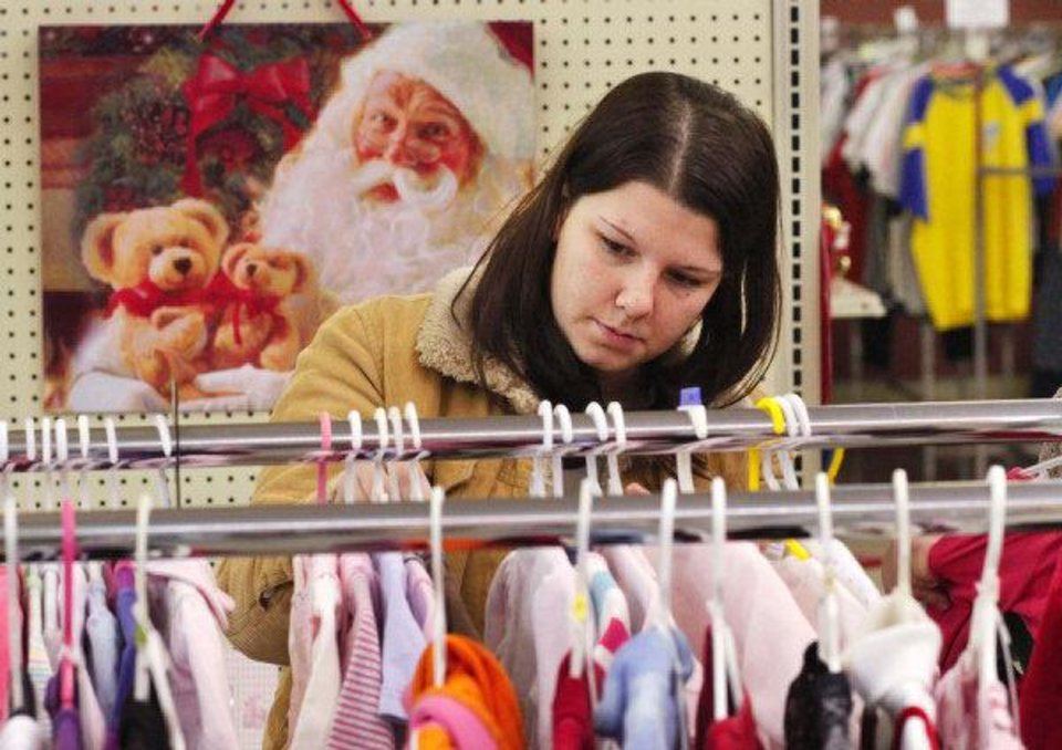 Photo - Hope Schiebert looks through racks of girls clothing as she shops for gifts for her three daughters at the Christmas Connection in southwest Oklahoma City.  JIM BECKEL - THE OKLAHOMAN