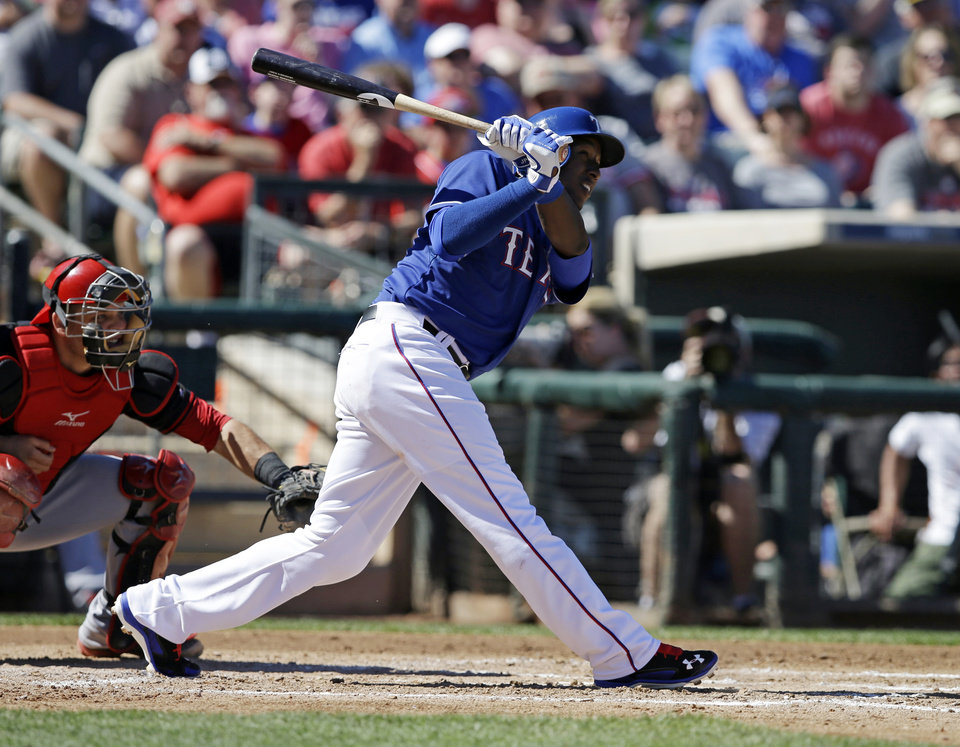 Photo - Texas Rangers' Jurickson Profar, right, watches a solo home run during the third inning of a spring exhibition baseball game against the Cincinnati Reds, Monday, March 10, 2014, in Suprise, Ariz. (AP Photo/Darron Cummings)