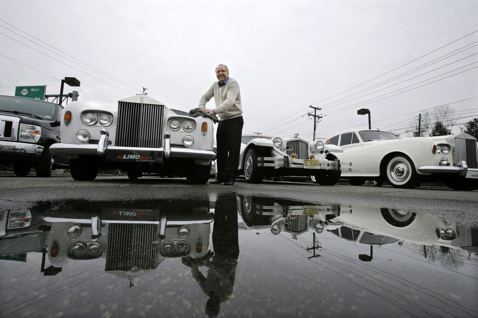 In this Tuesday, Jan. 15, 2013, photo, Joe Brasco, of  New Jersey Limo Bus & Limousine,wipes off a Rolls Royce in Fairfield, N.J. The flu season has created a scramble for New Jersey Limo Bus & Limousine as two of the company's seven full-time employees called in sick at the same time, but the Brascos have managed to find substitutes when workers have called in sick. (AP Photo/Mel Evans) ORG XMIT: NJME203