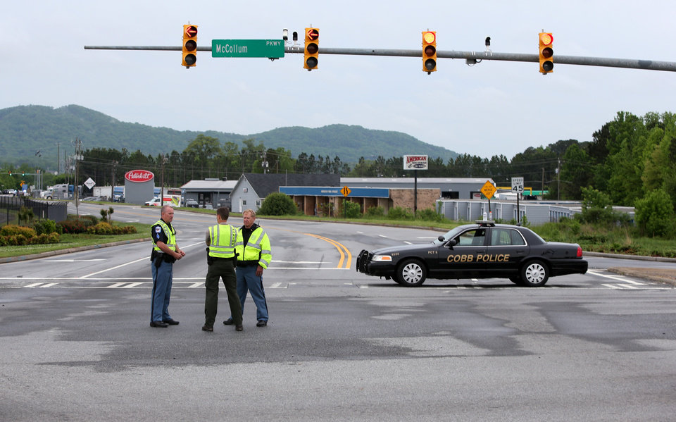 Photo - Cobb County Police block off Old US 41 Highway after an early morning workplace shooting at the Airport Road FedEx facility Tuesday April 29, 2014, in Kennesaw, Ga. A shooter opened fire at a FedEx center wounding at least six people before police swarmed the facility. The shooter was found dead from an apparent self-inflicted gunshot wound. (AP Photo/Jason Getz)