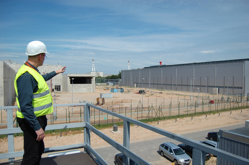 In this July 2012 photo, Thomas Pietsch, site manager for Nukem Technologies, a firm contracted for decommissioning projects for Lithuania's Soviet-era nuclear power plant, points to the unfinished nuclear fuel storage facility near the nuclear power plant in Ignalina, Lithuania. Three years after the nuclear plant was shut down due to safety concerns, there is still nuclear fuel inside one of the two reactors. The temporary storage facilities for spent fuel and radioactive waste are four years behind schedule. The problems have prompted threats from the European Union to sever funding and raising concerns that the facility will be around for years, possibly decades, longer than planned. The giant ventilation stacks in the background are part of the nuclear power plant. (AP Photo/Gary Peach)