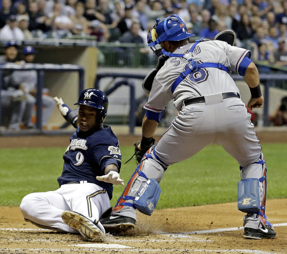 Photo - Texas Rangers catcher Geovany Soto (8) tags out Milwaukee Brewers' Jean Segura (9) at home during the third inning of a baseball game Wednesday, May 8, 2013, in Milwaukee. Segura tried to score from second on a hit by Aramis Ramirez. (AP Photo/Morry Gash)