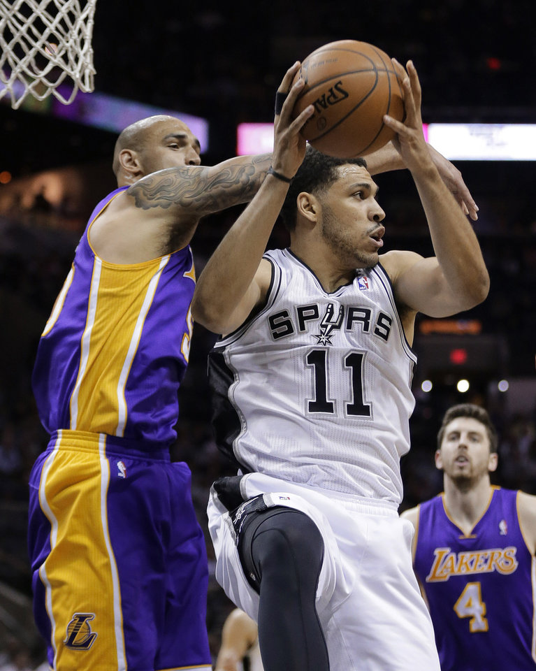 Photo - San Antonio Spurs' Jeff Ayres (11) pulls down a rebound in front of Los Angeles' Robert Sacre, left, during the first half of an NBA basketball game, Wednesday, April 16, 2014, in San Antonio. (AP Photo/Eric Gay)
