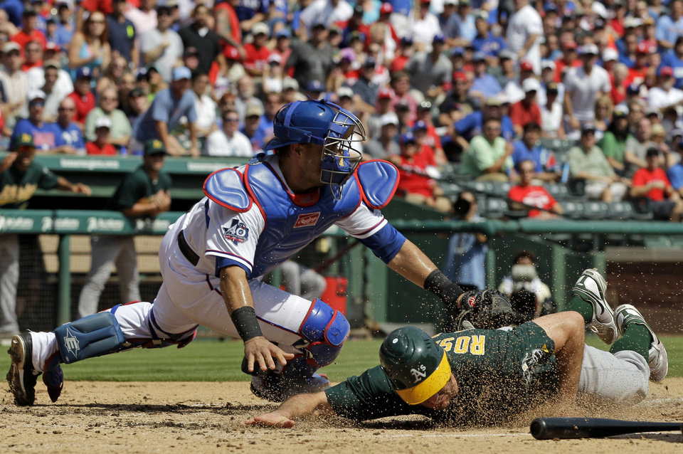 Photo -   Oakland Athletics' Adam Rosales scores at under the attempted tag by Texas Rangers' Geovany Soto during the third inning of a baseball game Thursday, Sept. 27, 2012, in Arlington, Texas. Rosales reached home safely on a Jonny Gomes double. (AP Photo/Tony Gutierrez)