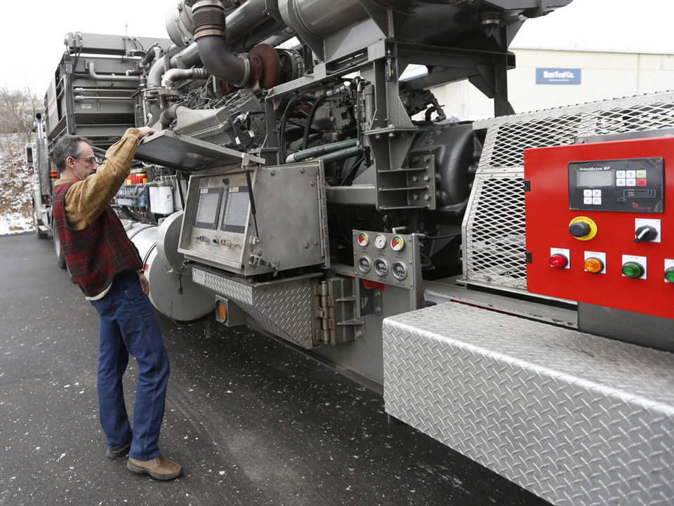 In this photo made on Thursday, Jan. 17, 2013, Universal Well Services fracturing engineering team leader Mike Michaelson opens the cover of a display panel before he starts the 16 cylinder diesel engine sfor the first time since it was converted to run on a blend of diesel and natural gas at the Cummins Bridgeway facility in Gibsonia, Pa. Since there was no natural gas available at this facility, the engine would run on diesel fuel alone this day. Oil- and gas-field companies from Pennsylvania to Texas are experimenting with converting the huge diesel engines that operate pumps that propel millions of gallons of water, sand and chemicals down a well bore in the fracturing process to break apart rock or tight sands that trap natural gas. (AP Photo/Keith Srakocic)