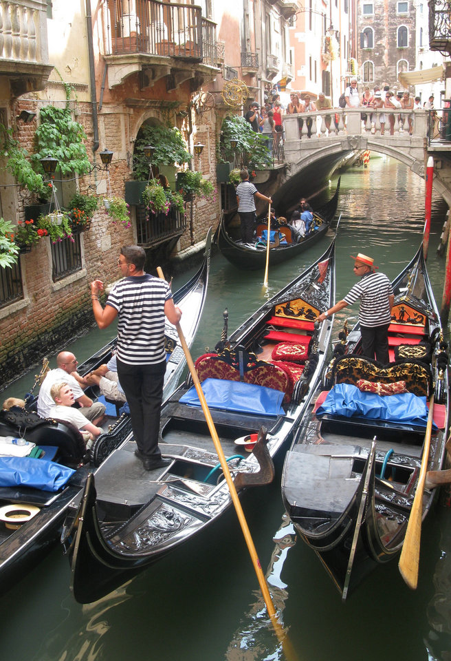 Photo - This July 15, 2012 photo shows Gondolas in a traffic jam on the narrow canals of Venice. To travel through northern Italy with a copy of Mark Twain's 1869 ''The Innocents Abroad', his classic 'record of a pleasure trip'. It took him to the great sights of Europe and on to Constantinople and Jerusalem before he sailed home to New York. Such a trip would take far too big a chunk out of my holiday time. But, Milan, Florence and Venice, a mere fragment for Twain, was within my reach for a two-week vacation. (AP Photo/Raf Casert)