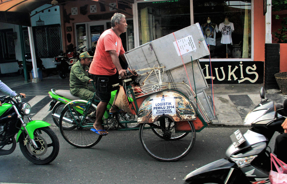 Photo - A tricycle driver transports ballot boxes that are being distributed to polling stations in Yogyakarta, Indonesia, Tuesday, July 8, 2014. As the world's third-largest democracy prepares to elect a new president Wednesday, Indonesians are divided between two very different choices: a former furniture maker, Jakarta Governor Joko Widodo and a wealthy ex-army general with close links to former dictator Suharto, Prabowo Subianto. (AP Photo/Slamet Riyadi)