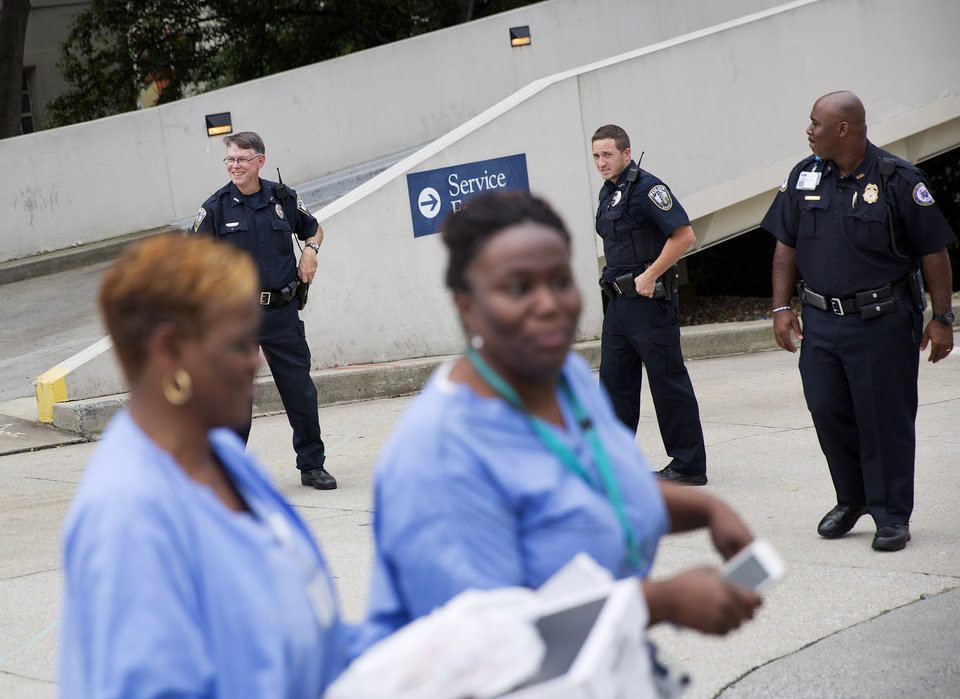 Photo - Hospital workers pass police officers guarding an entrance to Emory University Hospital after an ambulance arrived transporting an American that was infected with the Ebola virus, Saturday, Aug. 2, 2014, in Atlanta.  A specially outfitted plane carrying Dr. Kent Brantly from West Africa  arrived at a military base in Georgia. Brantly was taken to the Atlanta hospital.  Another American with Ebola is expected to join him at the hospital in a few days. (AP Photo/David Goldman)