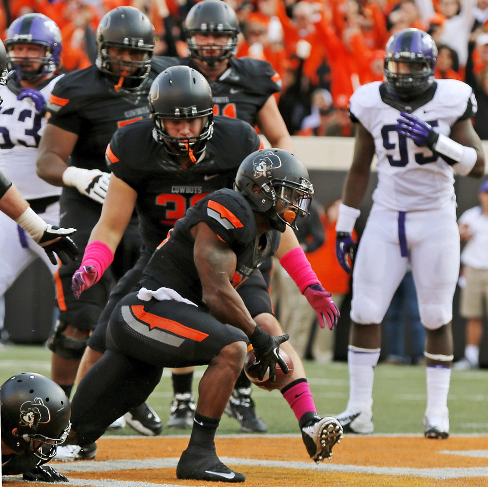 Photo - Oklahoma State's Jeremy Smith (31) gets up and tosses the ball to an official after scoring a touchdown in the third quarter during a college football game between Oklahoma State University (OSU) and Texas Christian University (TCU) at Boone Pickens Stadium in Stillwater, Okla., Saturday, Oct. 27, 2012. OSU won, 36-14. Photo by Nate Billings, The Oklahoman