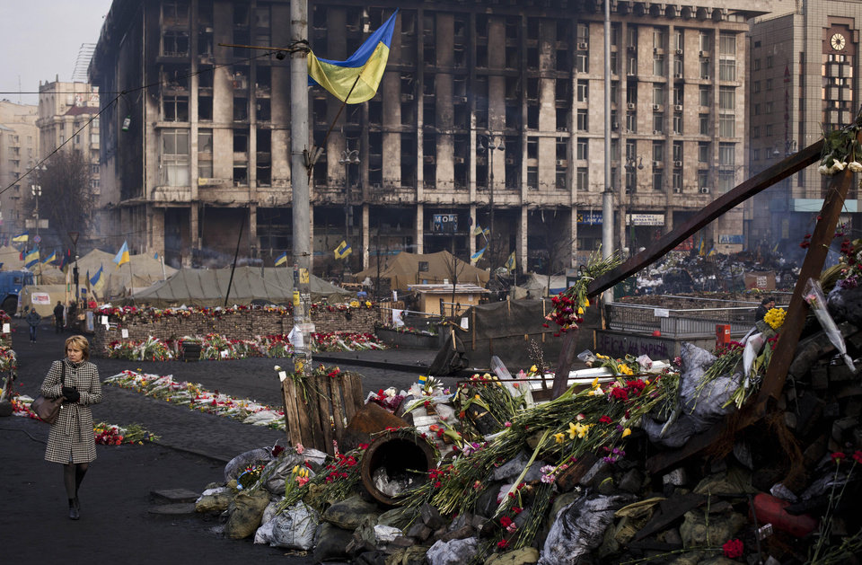 Photo - A woman walks past a barricade covered in flowers left to those killed in recent clashes in Kiev's Independence Square, Ukraine, Friday, March 7, 2014. In the background is the Trade Unions Building, which was damaged in a fire in late February. (AP Photo/David Azia)