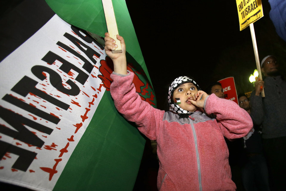 Karima Traish, 8, of Ashburn, Va., whose parents are Palestinian, protests against Israel's military action in Gaza, outside of the White House in Washington on Friday, Nov. 16, 2012, with a group of people organized by the ANSWER Coalition. (AP Photo/Jacquelyn Martin)