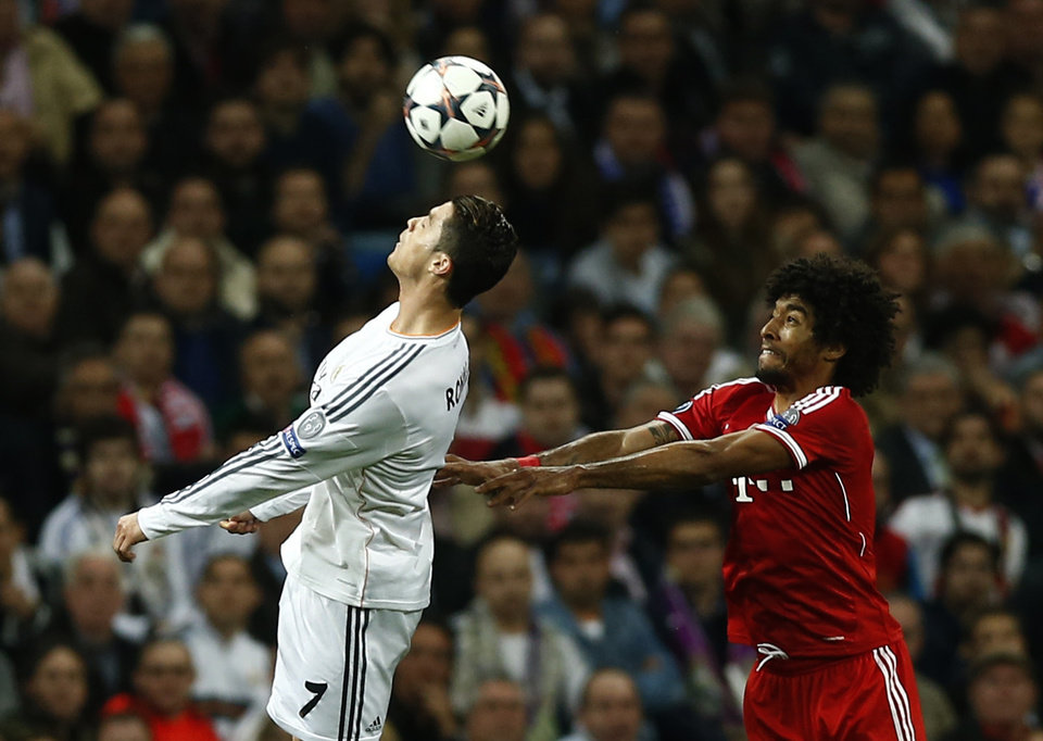 Photo - Real's Cristiano Ronaldo go for a header next to Bayern's Dante, right, during a first leg semifinal Champions League soccer match between Real Madrid and Bayern Munich at the Santiago Bernabeu stadium in Madrid, Spain, Wednesday, April 23, 2014. (AP Photo/Andres Kudacki)