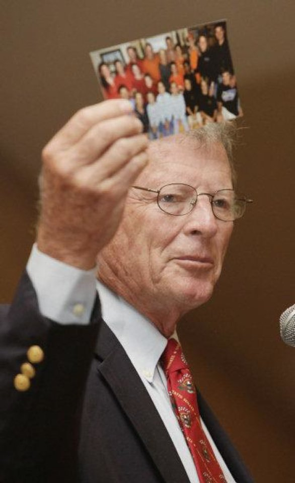 U.S. Sen. Jim Inhofe, R-Tulsa, holds up a family photo while speaking Thursday at a Greater Oklahoma City Chamber breakfast.  <strong>PAUL B. SOUTHERLAND - BY PAUL B. SOUTHERLAND</strong>