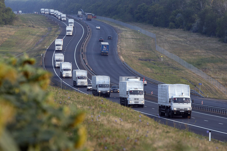 Photo - A convoy of white trucks with humanitarian aid moves from Voronezh towards Rostov-on-Don, Russia, early Thursday, Aug. 14, 2014. Russia on Tuesday dispatched some hundreds of trucks, although only a small proportion were counted in this convoy, covered in white tarps and sprinkled with holy water on a mission to deliver aid to a rebel-held zone in eastern Ukraine. (AP Photo/Pavel Golovkin)