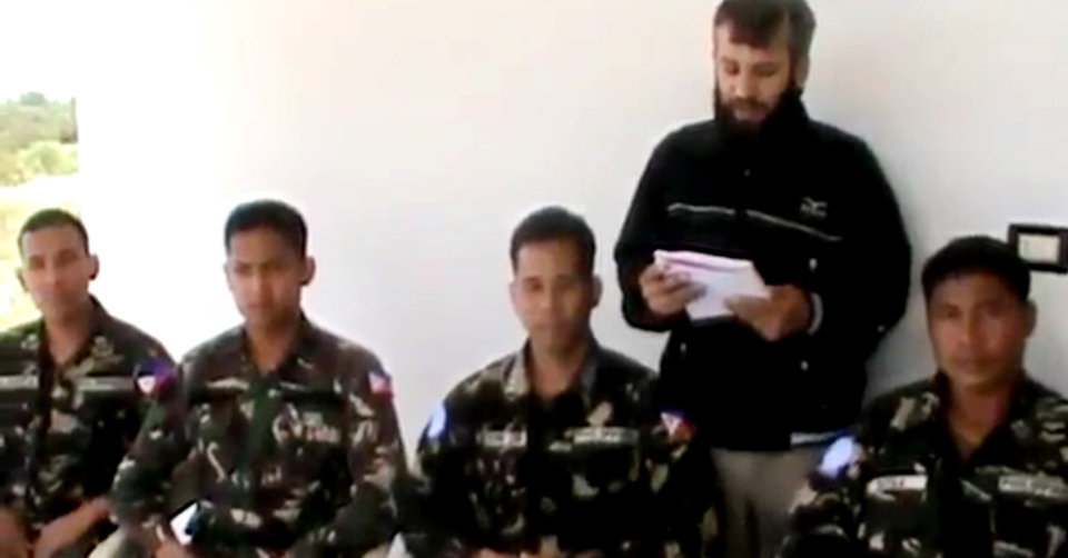 Photo - In this image taken from video obtained from the Ugarit News, which has been authenticated based on its contents and other AP reporting, a man reads a statement as four abducted Filipino UN peacekeepers are seen in Daraa, Syria, on Thursday, May 9, 2013. Tensions remained high on the Israeli-Syrian border on Thursday morning, two days after a Syrian rebel group abducted four UN peacekeepers. The abduction was the second such incident in the area in two months. The UN said the Filipino peacekeepers were detained on Tuesday while on patrol on the Golan Heights, a volatile Israeli-occupied area that separates Syria and Israel. (AP Photo/Ugarit News via AP video)