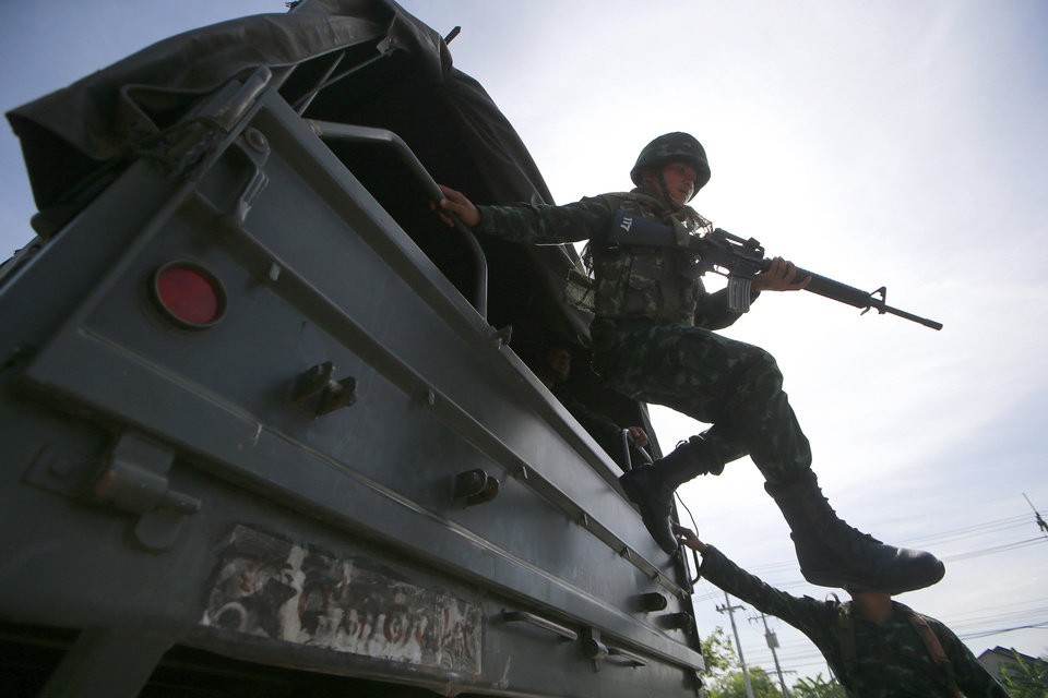 Photo - A Thai soldier jumps off a military truck after arriving at a pro-government rally site on the outskirts of Bangkok, Thailand Tuesday, May 20, 2014. Thailand's army declared martial law before dawn Tuesday in a surprise announcement it said was aimed at keeping the country stable after six months of sometimes violent political unrest. The military, however, denied a coup d'etat was underway. (AP Photo/Wason Wanichakorn)