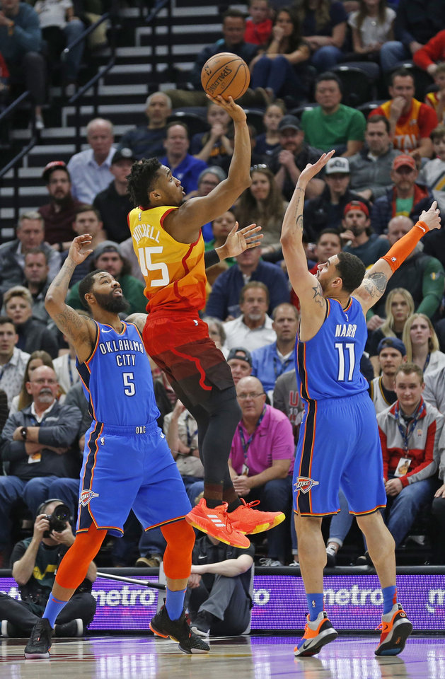Photo - Utah Jazz guard Donovan Mitchell (45) shoots as Oklahoma City Thunder's Markieff Morris (5) and Abdel Nader (11) defend in the first half during an NBA basketball game Monday, March 11, 2019, in Kearns, Utah. (AP Photo/Rick Bowmer)