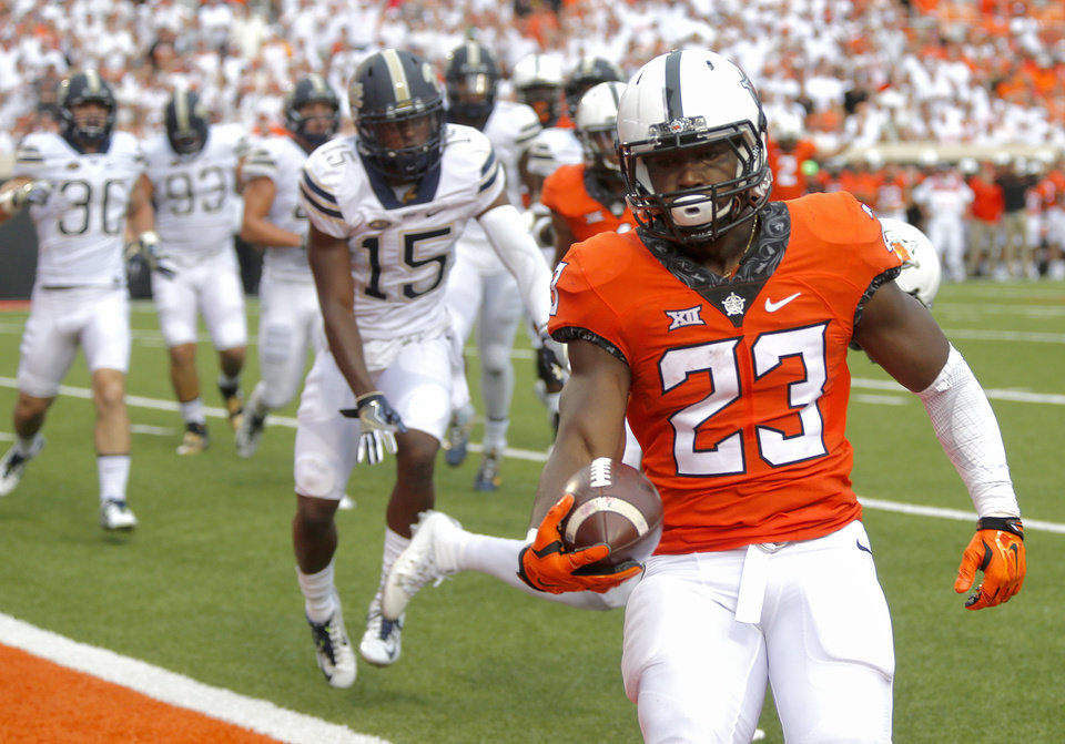 Photo - Oklahoma State's Rennie Childs (23) runs in for a touchdown during a college football game between the Oklahoma State Cowboys (OSU) and the Pitt Panthers at Boone Pickens Stadium in Stillwater, Okla., Saturday, Sept. 17, 2016. Photo by Chris Landsberger, The Oklahoman