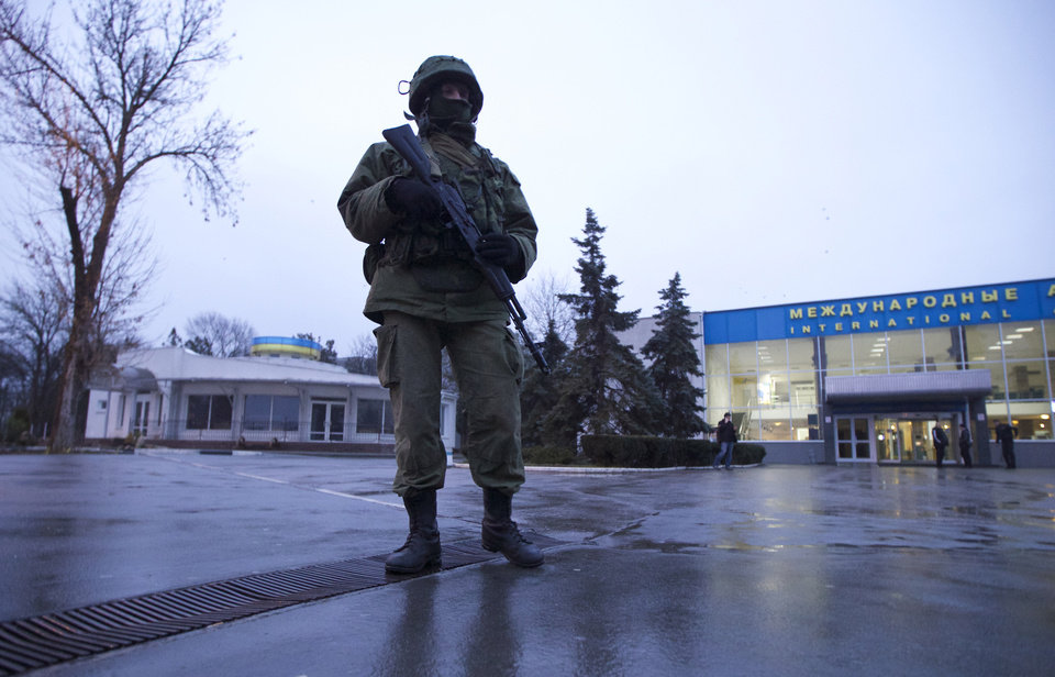 Photo - An unidentified armed man patrols a square in front of the airport in Simferopol, Ukraine, on Friday, Feb. 28, 2014.  Dozens of armed men in military uniforms without markings occupied the airport in the capital of Ukraine's strategic Crimea region early Friday. (AP Photo/Ivan Sekretarev)