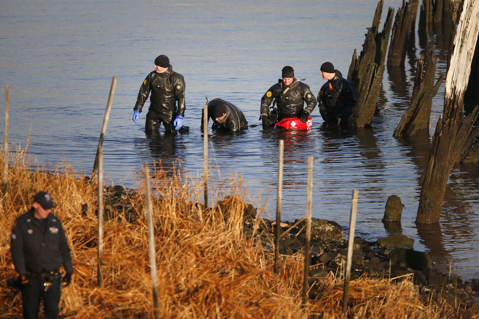 Photo - After discovering an arm, torso and legs Thursday, a New York Police Department dive unit continues the search for human remains along a rocky shoreline in the Queens borough of New York, Friday, Jan. 17, 2014.  Police were investigating whether the remains found Thursday could be those of autistic teen Avonte Oquendo, who walked out of his school and vanished more than three months ago, a law enforcement official said Friday. (AP Photo/Jason DeCrow)