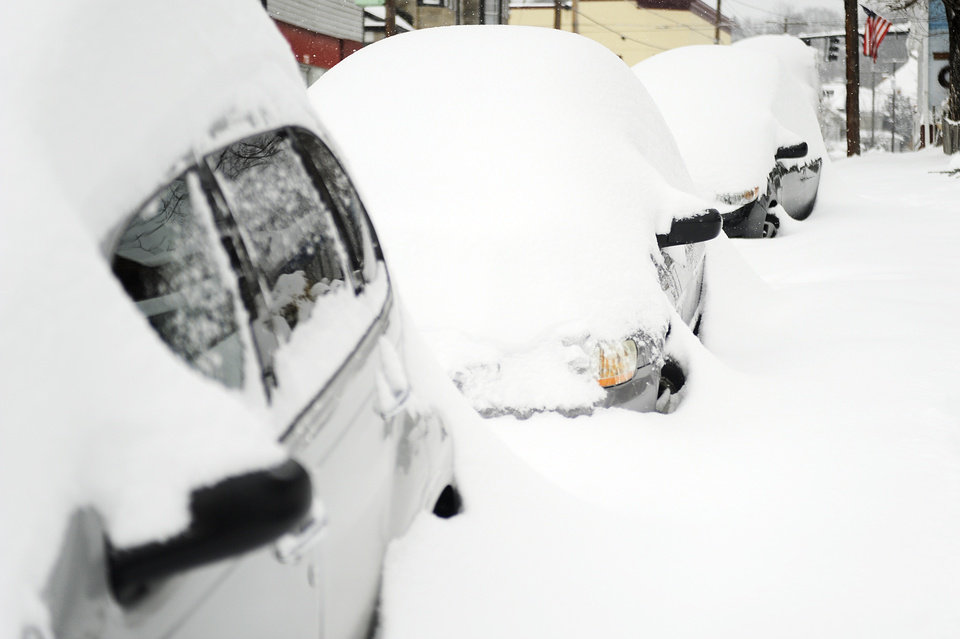 Photo - Vehicles are snow covered along Beverley Street after a snowstorm accumulating over a foot of snow on Thursday, Feb. 13, 2014, in Staunton, Va. (AP Photo/The News Leader, Katie Currid)