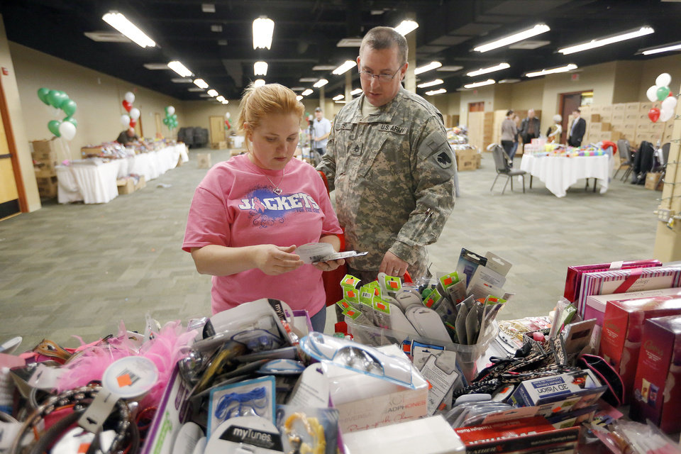 Photo - Left: Staff Sgt. Michael Baxter and his wife, Misty, shop for Christmas gifts  Tuesday at Operation Homefront distribution center at the Reed Center in  Midwest City. Photos by SARAH PHIPPS, The Oklahoman