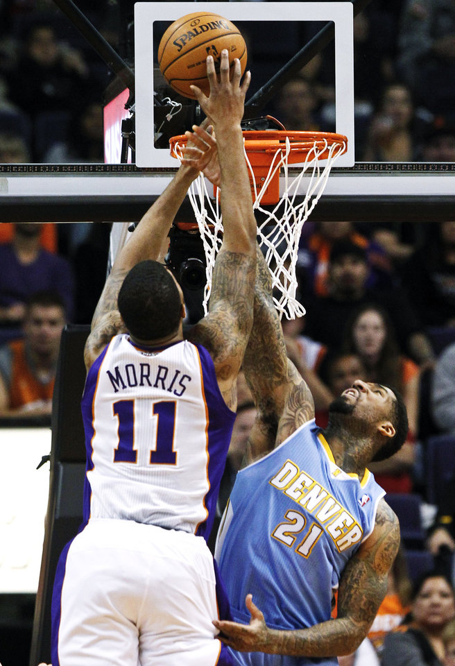 Photo -   Denver Nuggets' Wilson Chandler (21) blocks the shot of Phoenix Suns' Markieff Morris (11) in the first half of an NBA basketball game, Monday, Nov. 12, 2012, in Phoenix. (AP Photo/Ross D. Franklin)