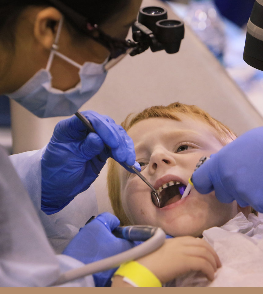 Photo -  A child looks nervously at Dr. Melanie Villalobos, left, and dental assistant Yvonne Streeter during the 2016 Oklahoma Mission of Mercy event. [OKLAHOMAN ARCHIVES PHOTO]