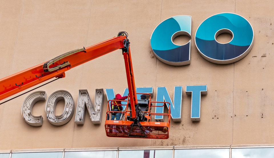 Photo -  Crews work to remove the Cox Convention Center name from the Prairie Surf Studios. The convention center has been converted to sound stages and production offices. [CHRIS  LANDSBERGER/THE OKLAHOMAN]