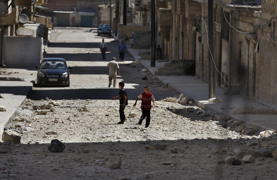 Photo -   RETRANSMISSION FOR ALTERNATIVE CROP -- Two Syrian boys play on a street next to a building hit by a Syrian government airstrike in Aleppo, Syria, Sunday, Aug. 19, 2012. (AP Photo/ Khalil Hamra)