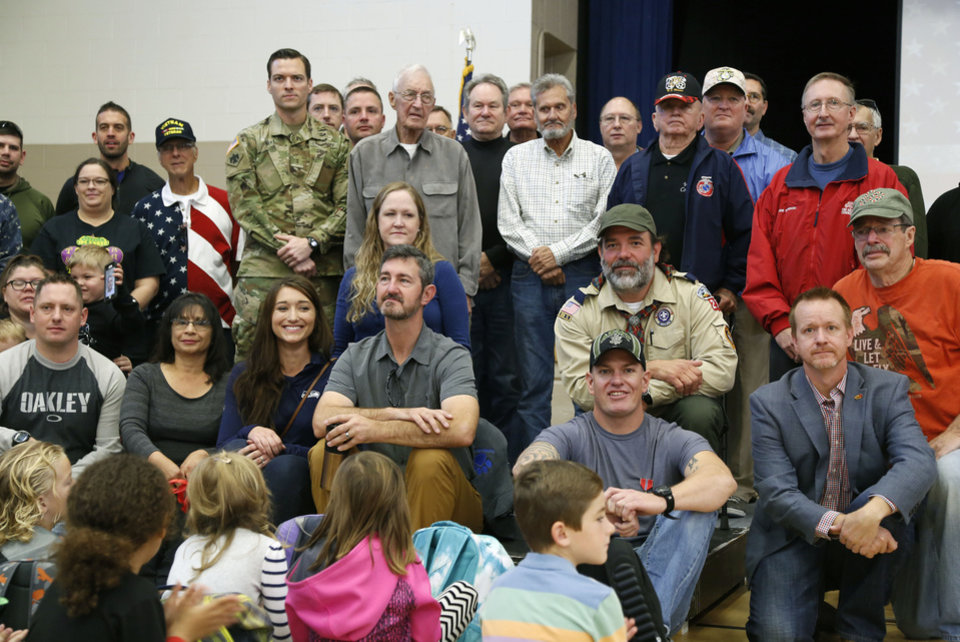 Photo -  Veterans pose for a photo during a Veterans Day assembly at Cleveland Elementary School in Norman last year. This Veterans Day, honorably discharged veterans will gain the privilege to shop service exchanges' online sites. [Photo by Paul Hellstern, The Oklahoman]