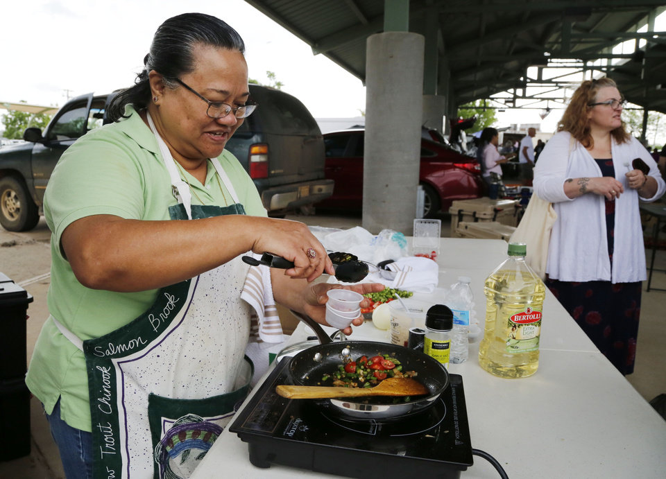 Photo -  Arlene Clifton cooks up samples of her asparagus and tomatoes of the first day of the season at Edmond Farmers Market. [PHOTO BY PAUL HELLSTERN, THE OKLAHOMAN]