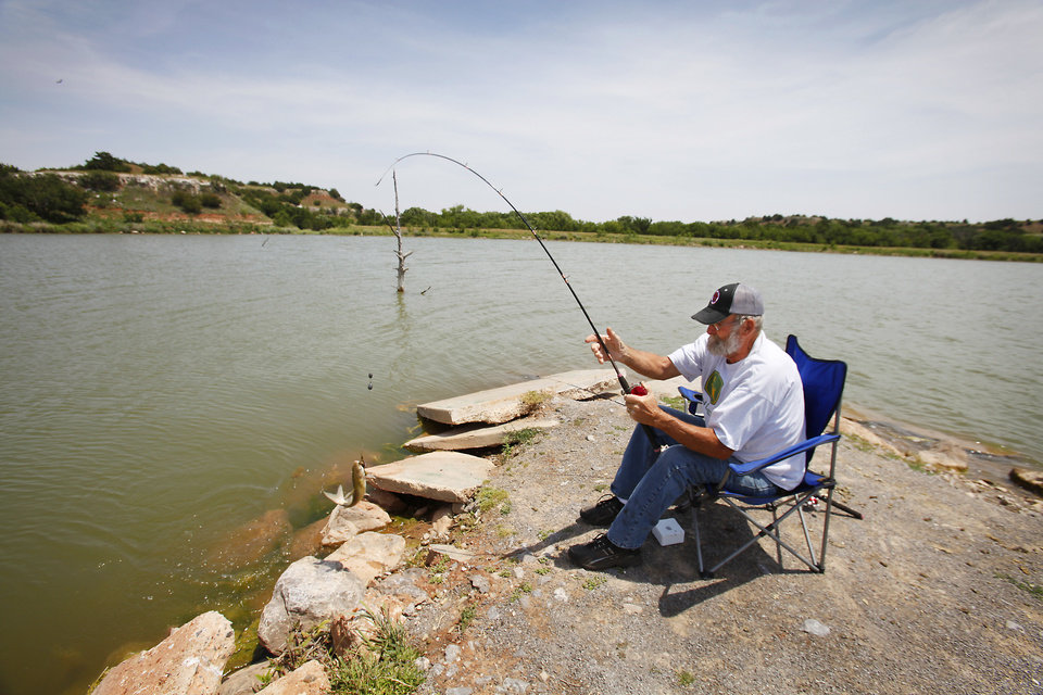Photo - Mickey Maddox, from Alva, pulls in a channel cat while fishing at Roman Nose State Park, Tuesday , May 22, 2012. Photo By David McDaniel/The Oklahoman