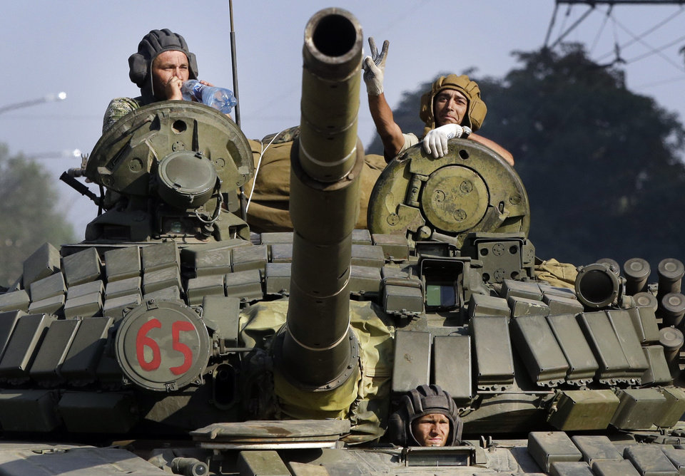 Photo - Pro-Russian rebels ride on a tank in the town of Krasnodon, eastern Ukraine, Sunday, Aug. 17, 2014. A column of several dozen heavy vehicles, including tanks and at least one rocket launcher, rolling through rebel-held territory on Sunday.(AP Photo/Sergei Grits)
