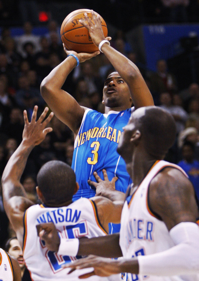 Photo - New Orleans Hornets' Chris Paul, center, shoots in front of Oklahoma City Thunder guard Earl Watson, left, and  Johan Petro, of France, right, in the first quarter of an NBA basketball game in Oklahoma City, Friday, Nov. 21, 2008. (AP Photo/Sue Ogrocki) ORG XMIT: OKSO101