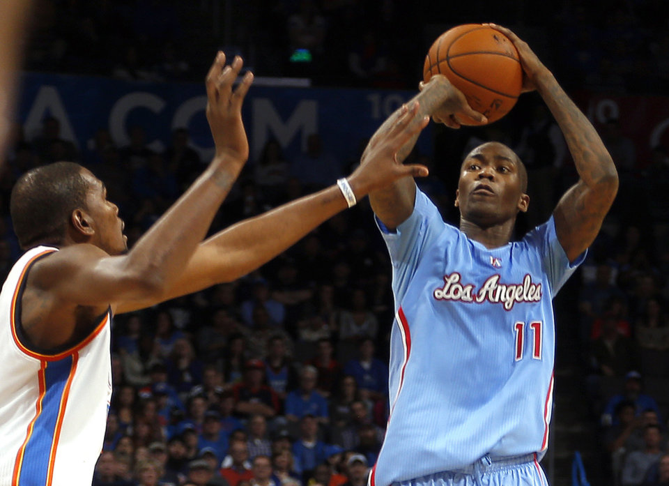 Photo - Los Angeles' Jamal Crawford (11) shoots as Oklahoma City 's Kevin Durant (35) defends during the NBA game between the Oklahoma City Thunder and the Los  Angeles Clippers at the Chesapeake Energy Arena, Sunday, Feb. 23, 2014. Photo by Sarah Phipps, The Oklahoman