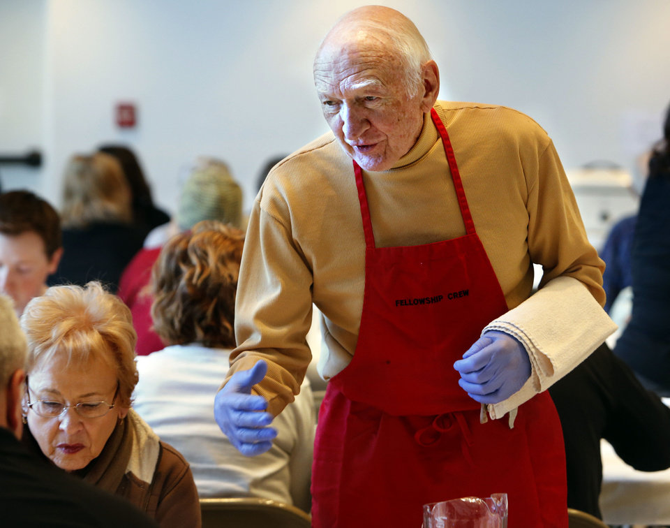 Photo - Verlin Meier waits tables Tuesday at the annual Benefit Bean Dinner  sponsored by the Men's Fellowship at First Christian Church in Norman.