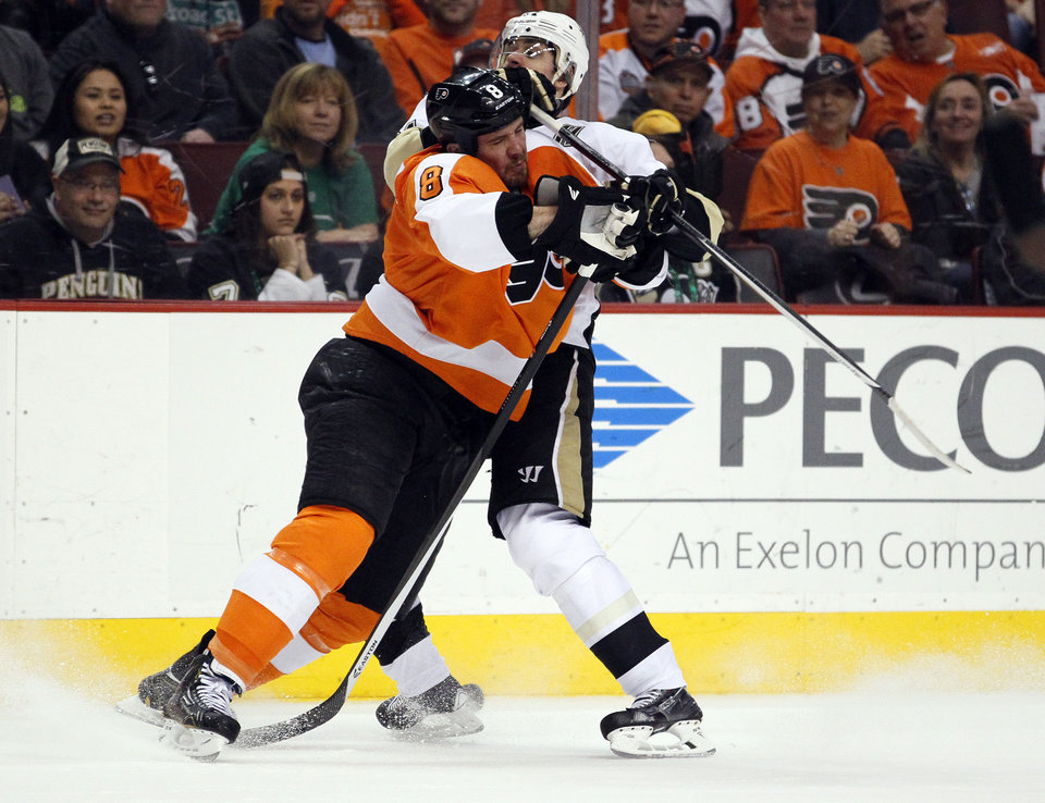 Photo - Philadelphia Flyers' Nicklas Grossmann, left and Pittsburgh Penguins' Evgeni Malkin collide along the boards during the first period of an NHL hockey game, Saturday, March 15, 2014, in Philadelphia. (AP Photo/Tom Mihalek)